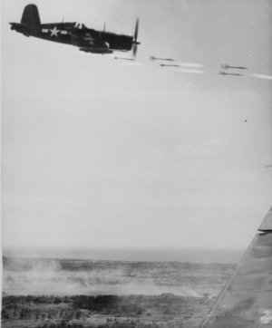 Corsair fighter looses its load of rocket projectiles on a run against a Japanese stronghold.